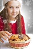 La muchacha hermosa de la Navidad quiere comer las galletas Foto de archivo