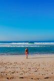 La muchacha hermosa de la persona que practica surf está disfrutando de vacaciones en la playa tropical Mujer joven con la tabla  Fotos de archivo libres de regalías