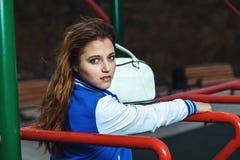 La muchacha hermosa de moda se coloca en la tierra de deportes Imagen de archivo libre de regalías