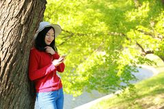 La muchacha hermosa de la mujer de la naturaleza china asiática linda feliz en un parque de la primavera disfruta de tiempo libre Imagen de archivo libre de regalías