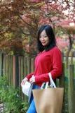 La muchacha hermosa de la mujer de la naturaleza china asiática linda feliz en un parque de la primavera disfruta de trenza del a Foto de archivo