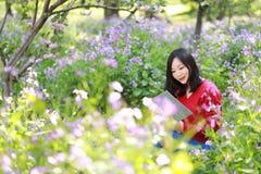 La muchacha hermosa de la mujer de la naturaleza china asiática linda feliz en un parque de la primavera goza del libro leído del Fotos de archivo
