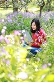 La muchacha hermosa de la mujer de la naturaleza china asiática linda feliz en un parque de la primavera goza del libro leído del Imagen de archivo