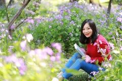 La muchacha hermosa de la mujer de la naturaleza china asiática linda feliz en un parque de la primavera goza del libro leído del Fotografía de archivo