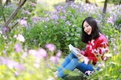 La muchacha hermosa de la mujer de la naturaleza china asiática linda feliz en un parque de la primavera goza del libro leído del Foto de archivo