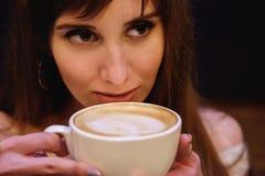 La muchacha hermosa de pelo largo en un suéter blanco se está colocando en una cafetería en una tabla de madera con una taza, ret foto de archivo