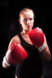 La muchacha hermosa defiende en guantes de boxeo Foto de archivo