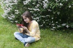 La muchacha hermosa del adolescente con la tableta se sienta en la hierba en parque foto Imagen de archivo