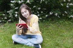 La muchacha hermosa del adolescente con la tableta se sienta en la hierba en parque foto Foto de archivo