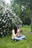 La muchacha hermosa del adolescente con la tableta se sienta en la hierba en parque foto Fotos de archivo