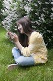 La muchacha hermosa del adolescente con la tableta se sienta en la hierba en parque foto Fotografía de archivo libre de regalías