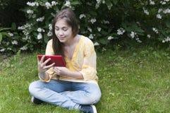 La muchacha hermosa del adolescente con la tableta se sienta en la hierba en parque foto Imágenes de archivo libres de regalías