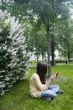 La muchacha hermosa del adolescente con la tableta se sienta en la hierba en parque foto Imagenes de archivo