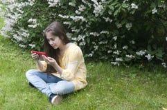 La muchacha hermosa del adolescente con la tableta se sienta en la hierba en parque foto Fotos de archivo libres de regalías