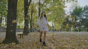 La muchacha hermosa del adolescente que sonríe y que camina con amarillo descendente del otoño se va en parque en la cámara lenta almacen de video