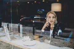 La muchacha hermosa del inconformista está llamando por teléfono vía el teléfono elegante, mientras que se está sentando en la ta Imagenes de archivo