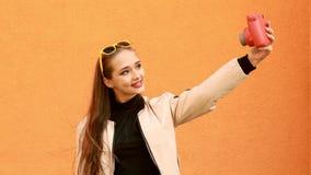 La muchacha hermosa del inconformista hace selfy por la cámara instantánea Fondo anaranjado outdoor metrajes