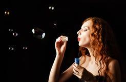 La muchacha hermosa del pelirrojo sopla burbujas fotografía de archivo