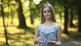 La muchacha hermosa del pelo rubio que se sienta en taburete y dibuja una imagen en el parque usando una paleta con pinturas y un almacen de metraje de vídeo