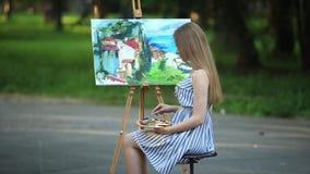 La muchacha hermosa del pelo rubio que se sienta en taburete y dibuja una imagen en el parque usando una paleta con pinturas y un metrajes