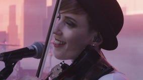La muchacha hermosa del primer de la cámara lenta en sombrero toca el violín y canta metrajes