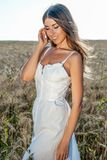 La muchacha hermosa del verano en un campo de trigo, en un vestido blanco, bronceó la piel, feliz el vacaciones en el aire fresco Fotografía de archivo