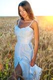 La muchacha hermosa del verano en un campo de trigo, en un vestido blanco, bronceó la piel, feliz el vacaciones en el aire fresco Fotografía de archivo libre de regalías