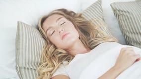 La muchacha hermosa despierta en su cama temprano por la mañana y estira metrajes