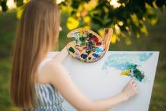 La muchacha hermosa dibuja una imagen en el parque usando una paleta con pinturas y una espátula Caballete y lona con una imagen  imágenes de archivo libres de regalías