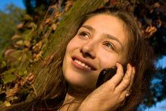 La muchacha hermosa dice en el móvil Imagen de archivo