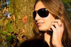 La muchacha hermosa dice en el móvil Fotos de archivo libres de regalías