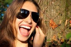 La muchacha hermosa dice en el móvil Foto de archivo libre de regalías