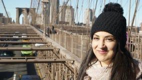 La muchacha hermosa disfruta del paseo sobre el puente de Brooklyn Nueva York almacen de video