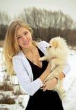 La muchacha hermosa el blonde con un perro en las manos Foto de archivo
