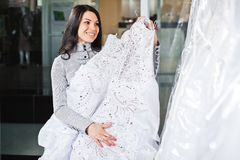 La muchacha hermosa elige su vestido de boda Retrato en el sa nupcial foto de archivo libre de regalías