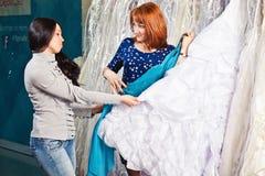 La muchacha hermosa elige su vestido de boda Retrato en el sa nupcial fotos de archivo libres de regalías