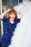 La muchacha hermosa elige su vestido de boda Retrato en el sa nupcial Imagen de archivo