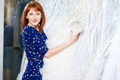 La muchacha hermosa elige su vestido de boda Retrato en el sa nupcial foto de archivo