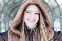 La muchacha hermosa en abrigo de pieles está sonriendo Fotos de archivo