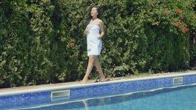 La muchacha hermosa en la albornoz blanca con el cóctel a disposición camina cerca de piscina metrajes