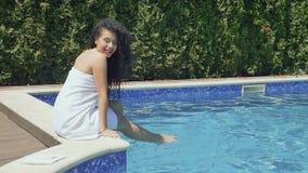 La muchacha hermosa en albornoz disfruta con agua que se sienta cerca de piscina azul almacen de video