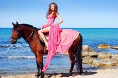 La muchacha hermosa en alineada roja se sienta en caballo Foto de archivo libre de regalías