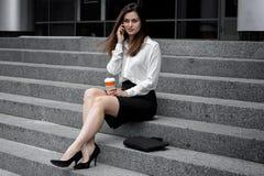 La muchacha hermosa en la camisa y la falda blancas se sienta en los pasos y en el teléfono Fotos de archivo libres de regalías