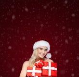 La muchacha hermosa en casquillo de la Navidad lleva a cabo un sistema de presentes Fotos de archivo