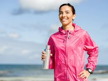 La muchacha hermosa en deporte viste el agua potable después de entrenamiento en la playa Fotos de archivo