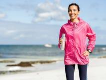 La muchacha hermosa en deporte viste el agua potable después de entrenamiento en la playa Imagenes de archivo