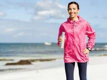 La muchacha hermosa en deporte viste el agua potable después de entrenamiento en la playa Fotografía de archivo