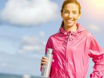 La muchacha hermosa en deporte viste el agua potable después de entrenamiento en la playa Imágenes de archivo libres de regalías