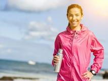 La muchacha hermosa en deporte viste el agua potable después de entrenamiento en la playa Foto de archivo