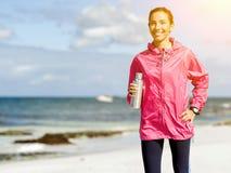 La muchacha hermosa en deporte viste el agua potable después de entrenamiento en la playa Foto de archivo libre de regalías
